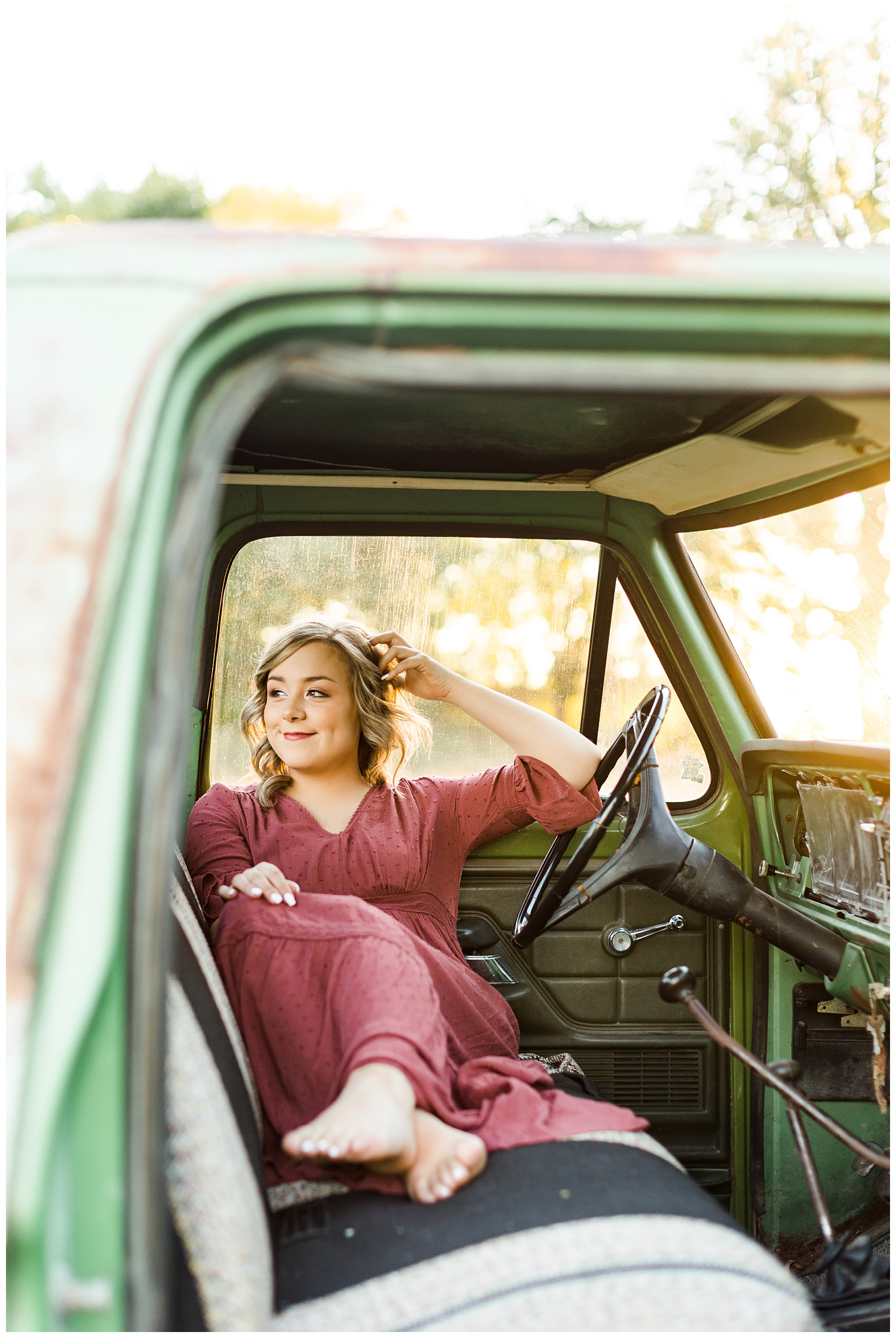Cloey, wearing a vintage red dress, sits in an old, rusty green truck at golden hour   CB Studio
