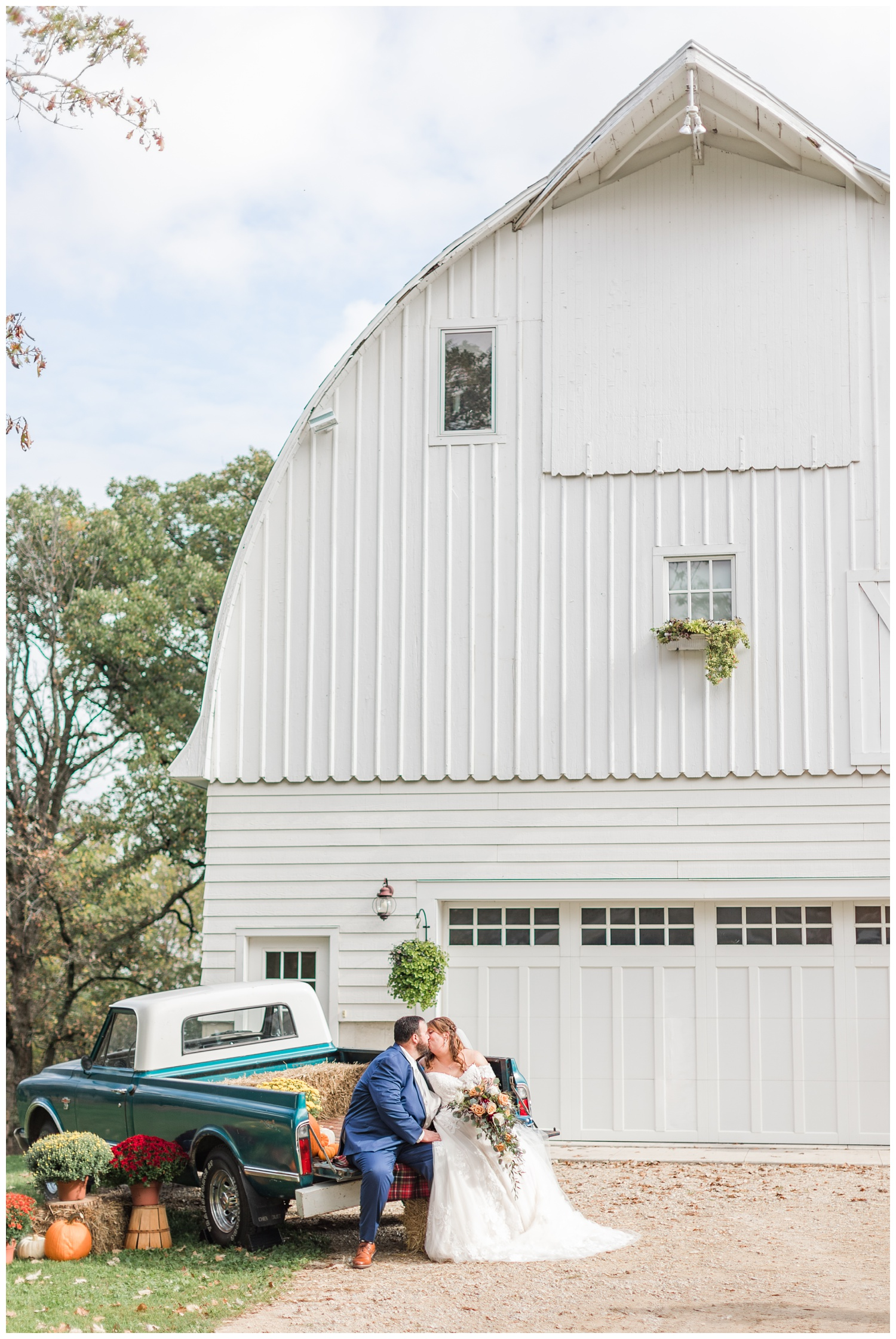 Bride and groom kiss in the back of an old Chevy truck in front of the white barn at Diamond Oak Events | CB Studio