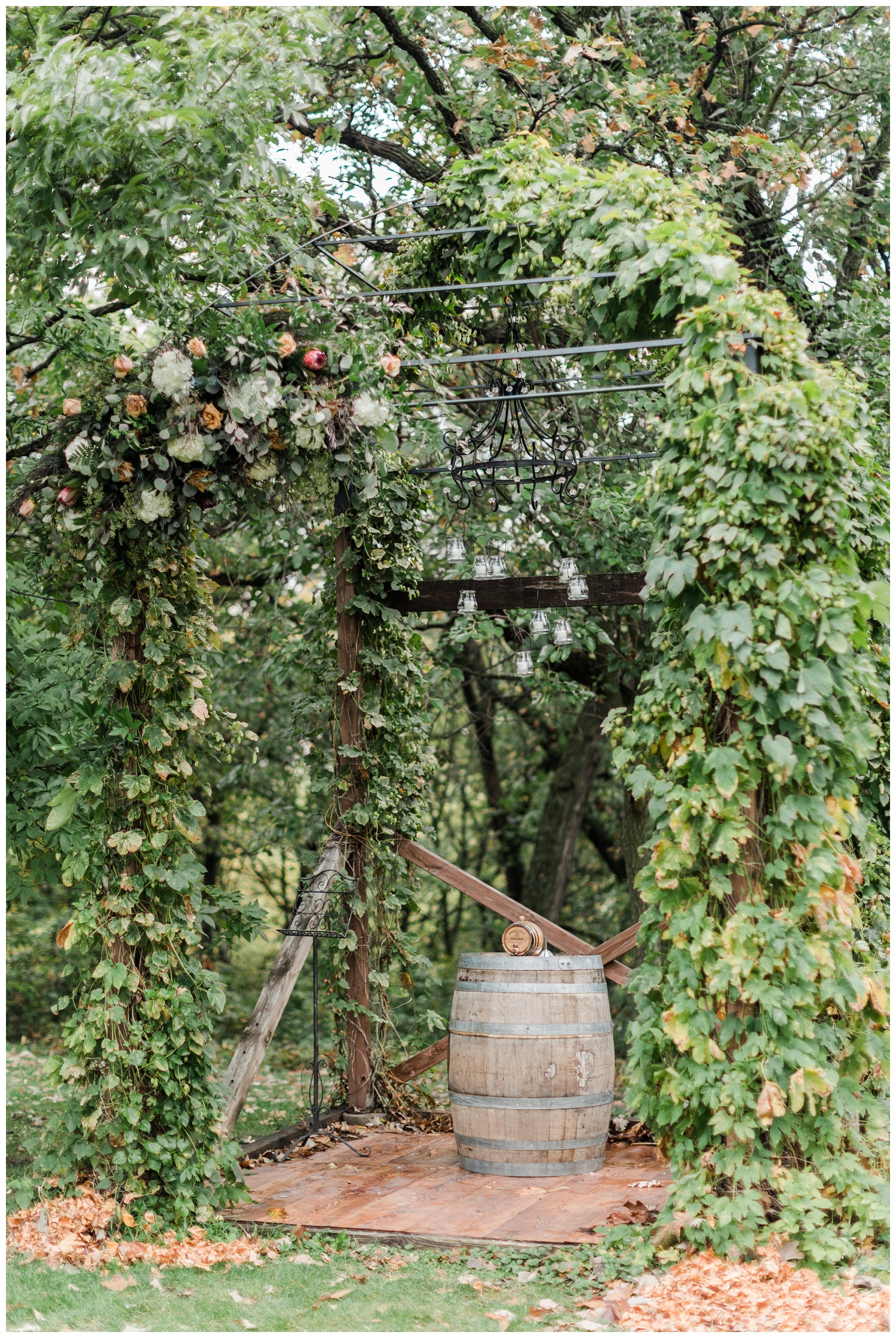 Wedding ceremony arch covered in florals and vines surrounded by oak trees featuring a whiskey barrel and candlelit chandelier at Diamond Oak Events | CB Studio