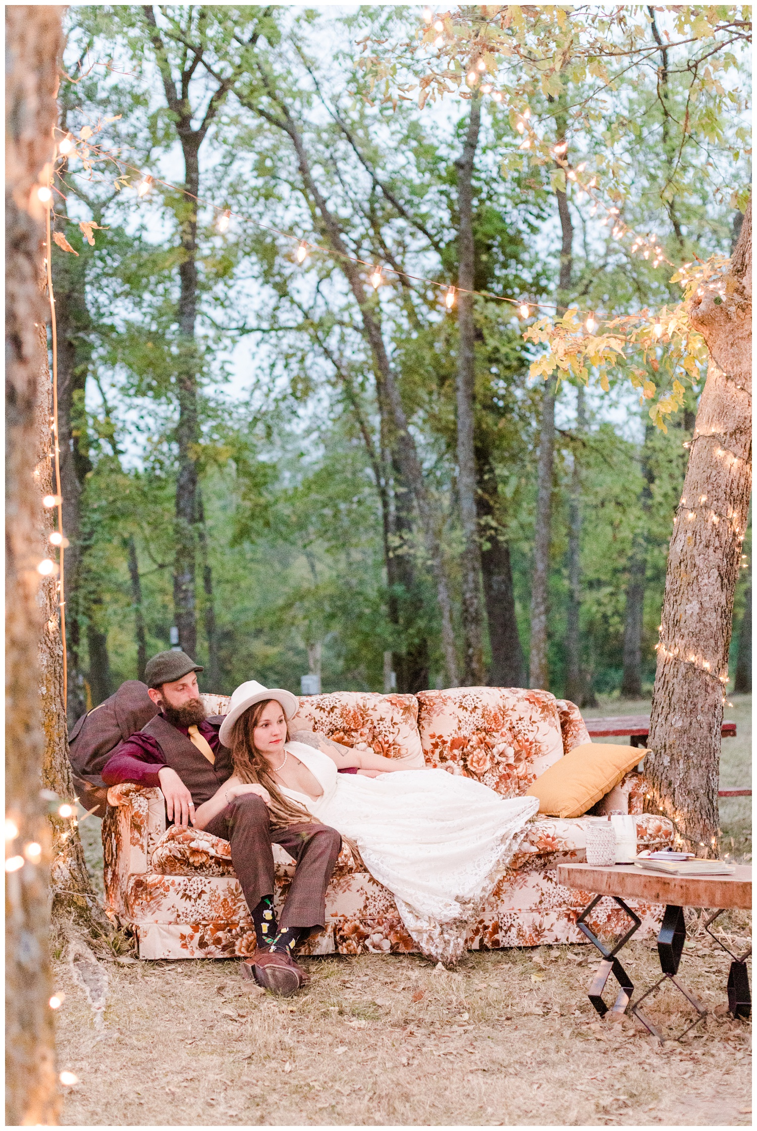 Authentic Boho Hippie bride and groom lay on a vintage couch in the woods   CB Studio