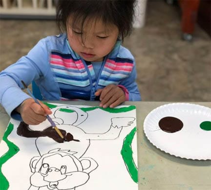 Four years old girl painting in art class.
