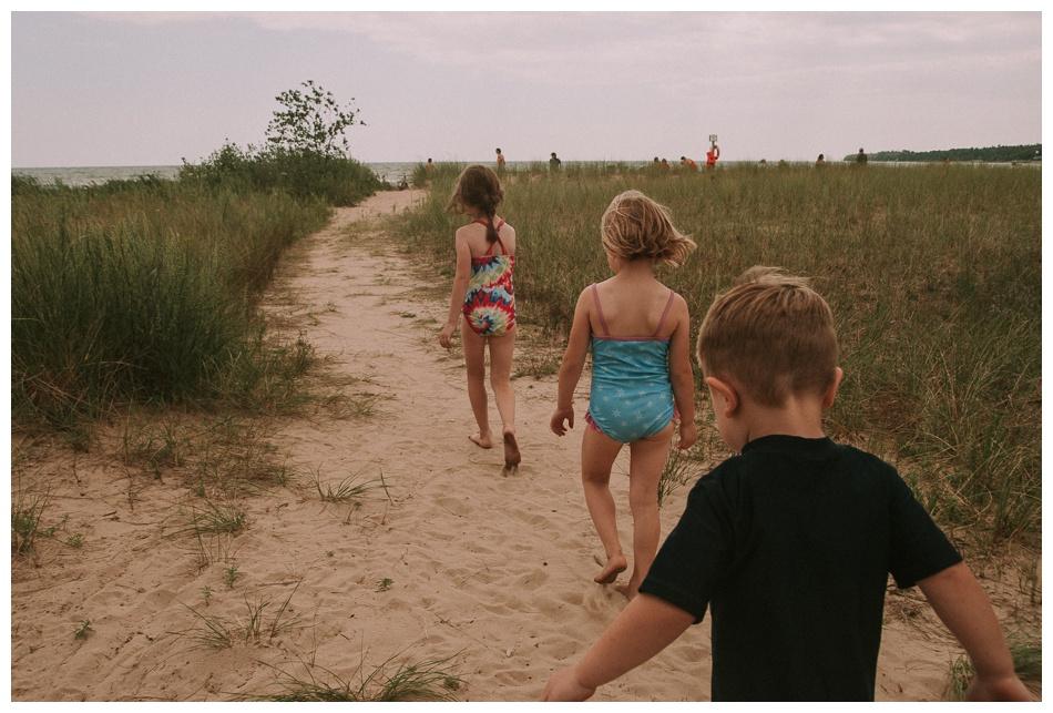 Three kids walk along the beach.