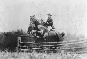 Black and white photo of Theodore Roosevelt and Capt Fitzhugh on horses, jumping a fence, 1907.