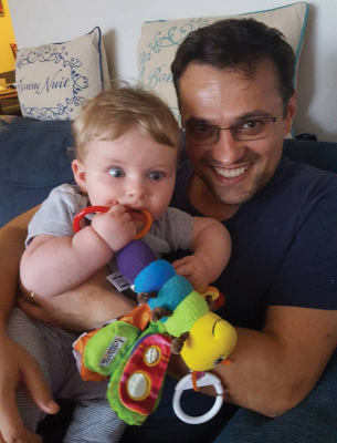 Marius holding friends' baby, who is chewing on a stuffed firefly toy