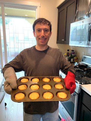 Neil holding a baking tray in kitchen