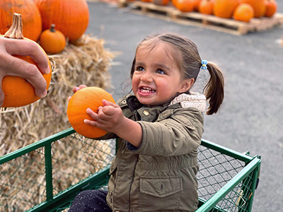 Reya holding a pumpkin and smiling