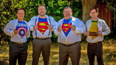 Men with dress shirts unbuttoned to reveal super hero costumes