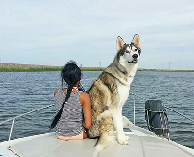 Paula sitting on prow with dog, Timber