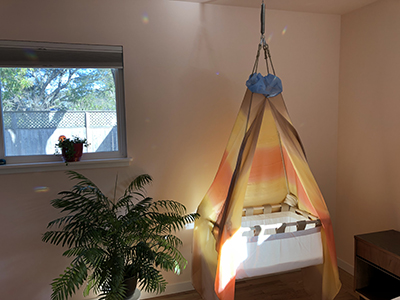 Baby cradle with hanging curtains in Anna and Greg's nursery