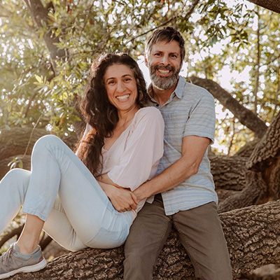 Greg and Anna sitting together on a tree branch