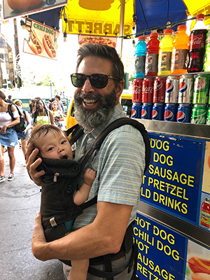 Greg in front of hot dog stand holding a friend's baby