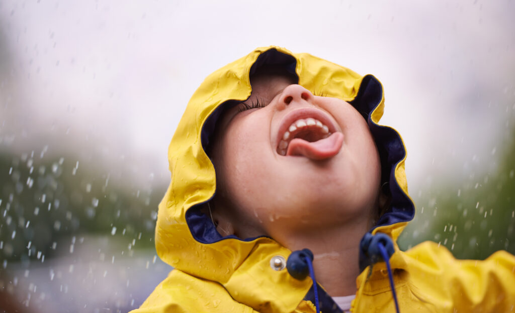 boy with mouth open to lick rain