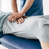 chiropractor massaging back of man on Massage Table in hospital