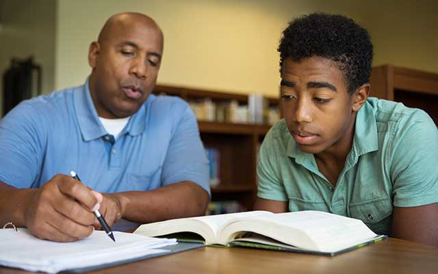 African-American teacher assisting African-American student