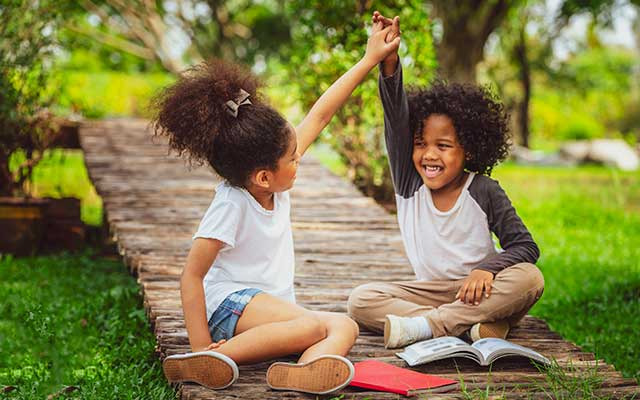 young boy and girl hi five