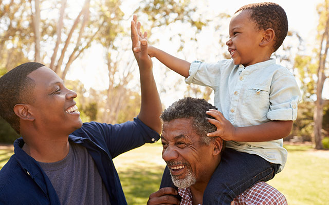 African-American father, grandfather and son playing in park