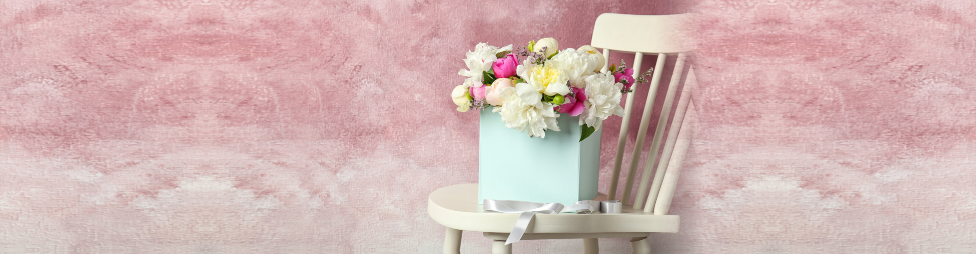 Box with beautiful flowers on wooden chair against color background