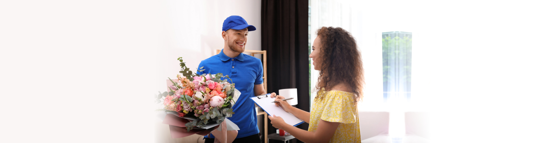 African-American woman receiving flower bouquet from delivery man