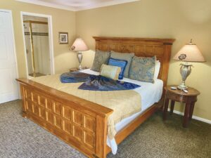 the king bed in suite 7 with a large head and foot board, the entrance into the bath in the background