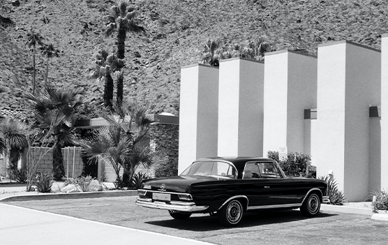 vintage grayscale photography of gray coupe parked in front of white building