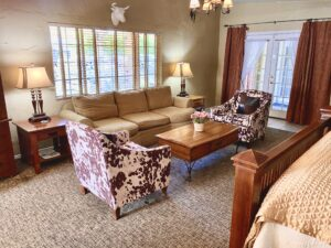 the large living room of Suite 1 featuring a 3 person sofa, two cow print chairs, a coffee table, two end tables with lamps and french doors in the background
