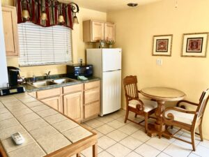 The kitchenette of suite 1 featuring a table for two, large cabinets and counters with lots of room, Refrigerator, Microwave, and Keurig Coffeemaker
