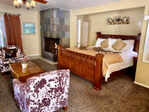 the sleeping area of Suite 1 featuring a king sized bed with a fireplace in the background next to the bed.