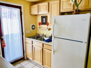 The kitchenette of suite 2 featuring a sink, large refrigerator, microwave, and a Keurig Coffeemaker.