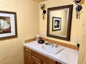 The vanity of suite 3 featuring a large mirror and a tiled countertop.