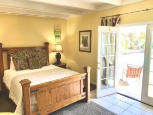 The queen bed in suite 4 with an open set of French doors on the right that lead out to the pool area.