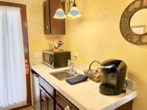 The kitchenette of suite 4 featuring a microwave, sink, fridge and a Keurig Coffeemaker