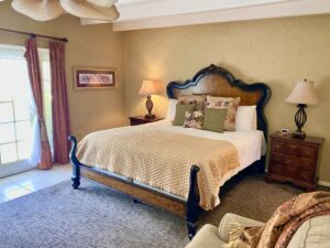 The king bed in suite 8 with the doors that open into the pool area in the background
