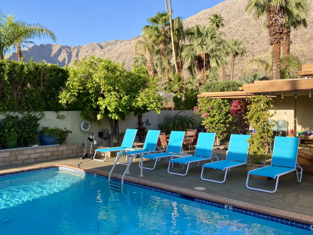 the pool featuring lounge chairs, great landscaping, palm trees, mountains and blue skies.