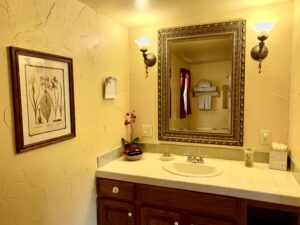 The vanity of suite 5 featuring a large mirror and a tiled countertop.