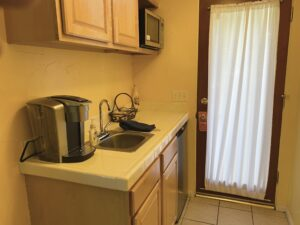 The kitchenette of suite 5 featuring a microwave, sink, fridge and a Keurig Coffeemaker