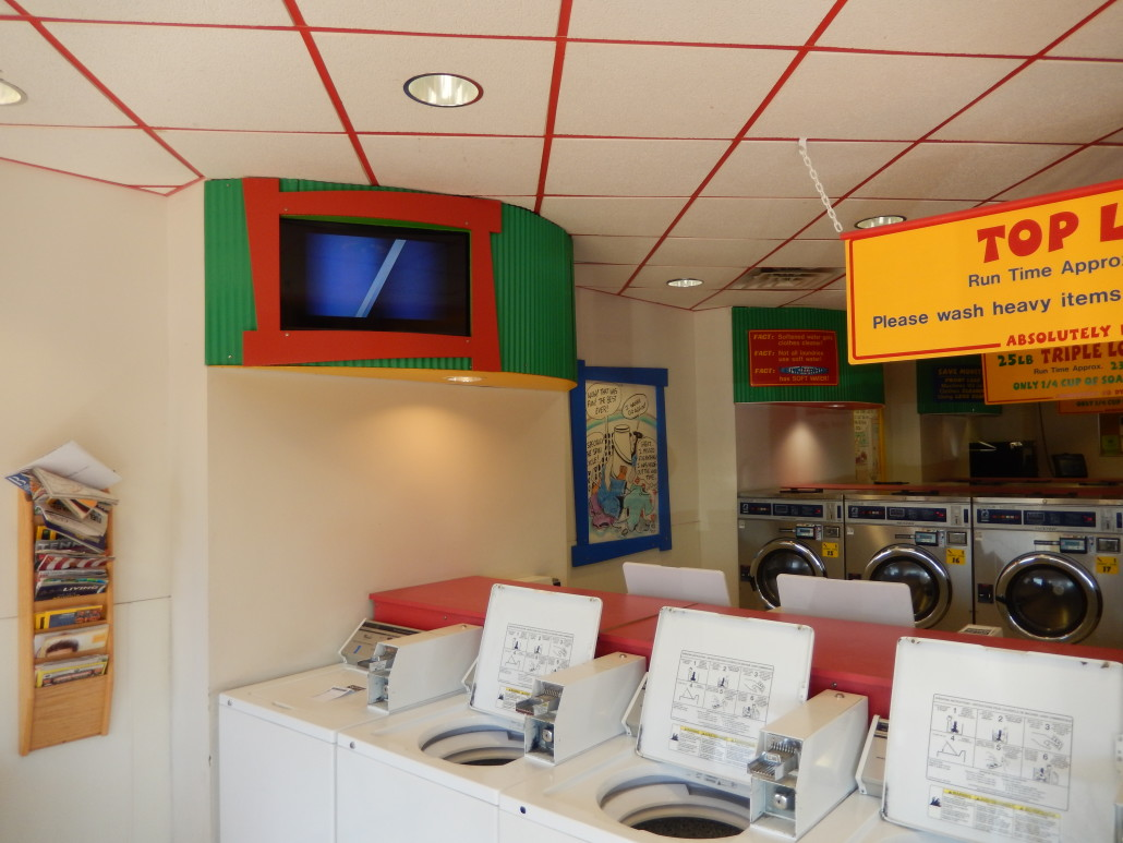 TVs by top load washing machines at Walden Square Laundromania West Iowa City