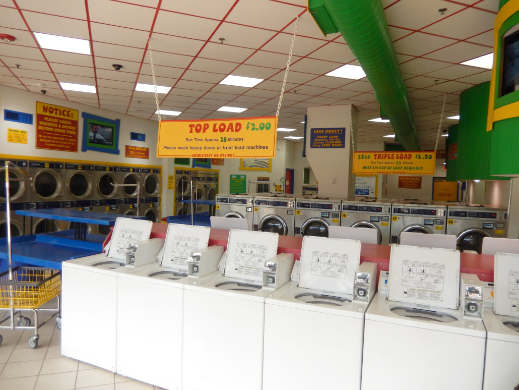 Inside Laundromania in North Liberty Iowa with top load washing machines