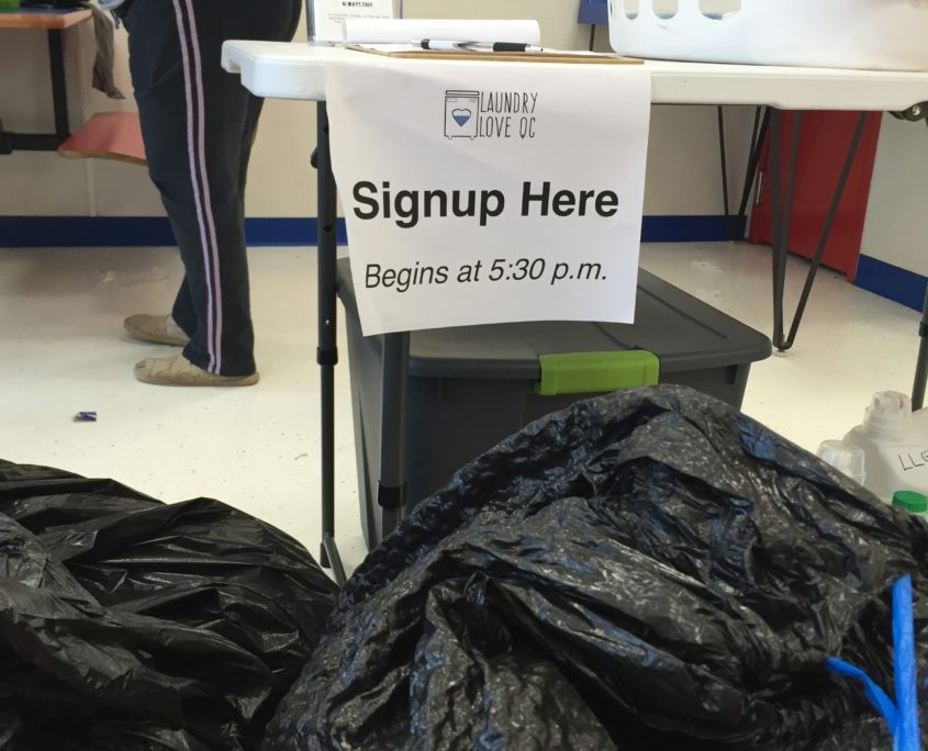 Signup here table for Laundry Love QC free laundry event at Laundromania in Davenport