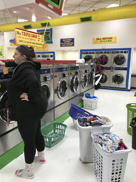 Loads of laundry in bins at Laundry Love QC event at Laundromania in Davenport, Iowa