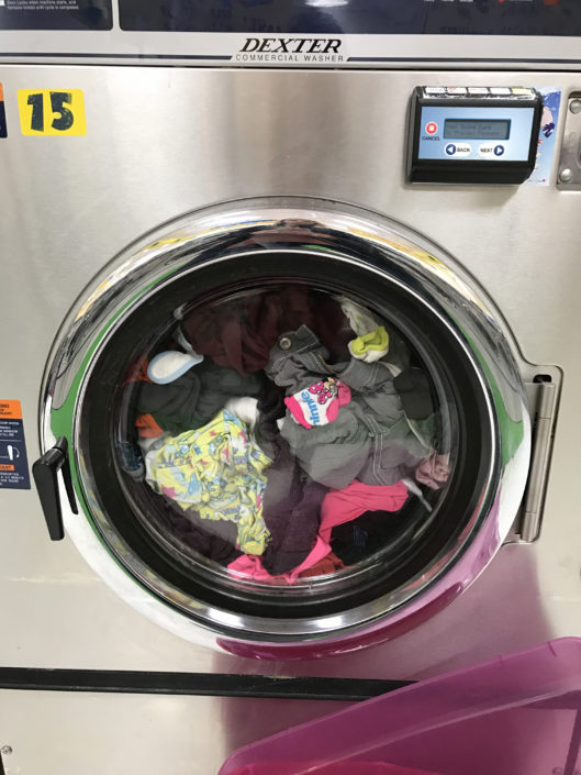 Washing machine with clothes at Laundry Love QC event at Laundromania in Davenport, Iowa