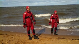 Louie and Chad in cold water suits exiting the water from standing by