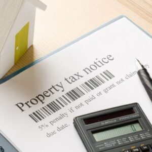 property tax document on the table with a pen, calculator and small house on the table
