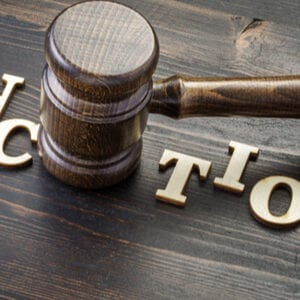 Image shows the word sanctions on a table with a judges gravel