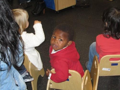 Little one listening to reading a St. Vincent De Paul Village, Child Development Center.