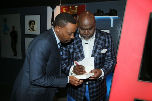 Bishop Jakes, signs a personalized copy for talk show host Arsenio Hall.  Photo courtesy of the Arsenio Hall Show.