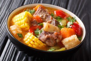 Delicious Sancocho thick meat soup with vegetables close-up in a bowl. horizontal