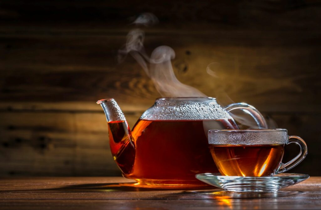 Clear glass pot and cup of steaming tea