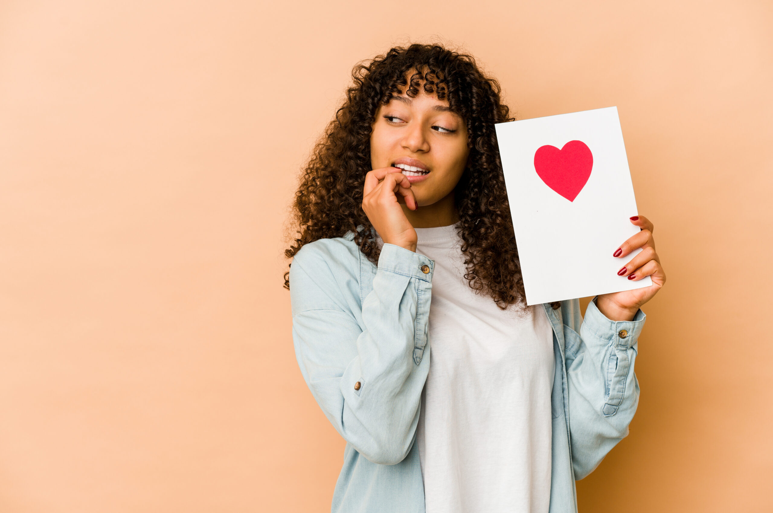self-care-black-woman-holding-a-valentines-day-card-standing-in-front-of-a-yellow-background