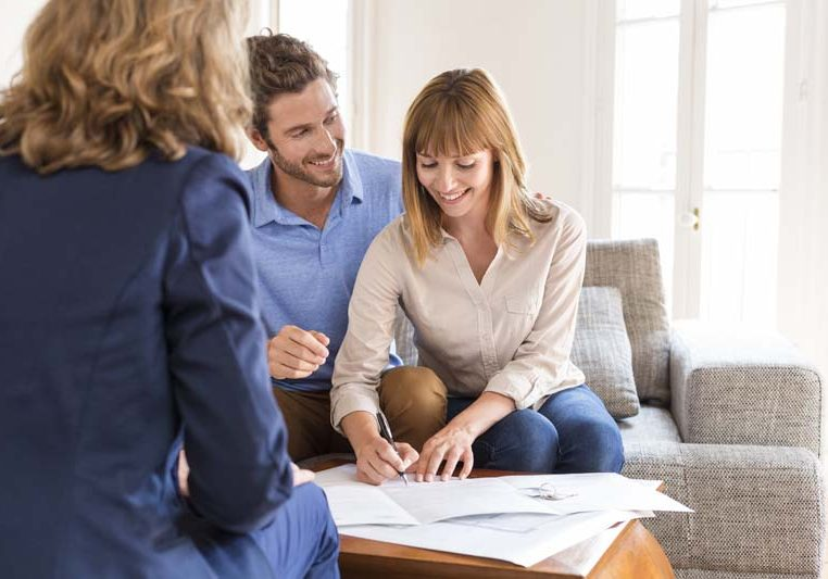 Young owners couple signing a contract for house investment.