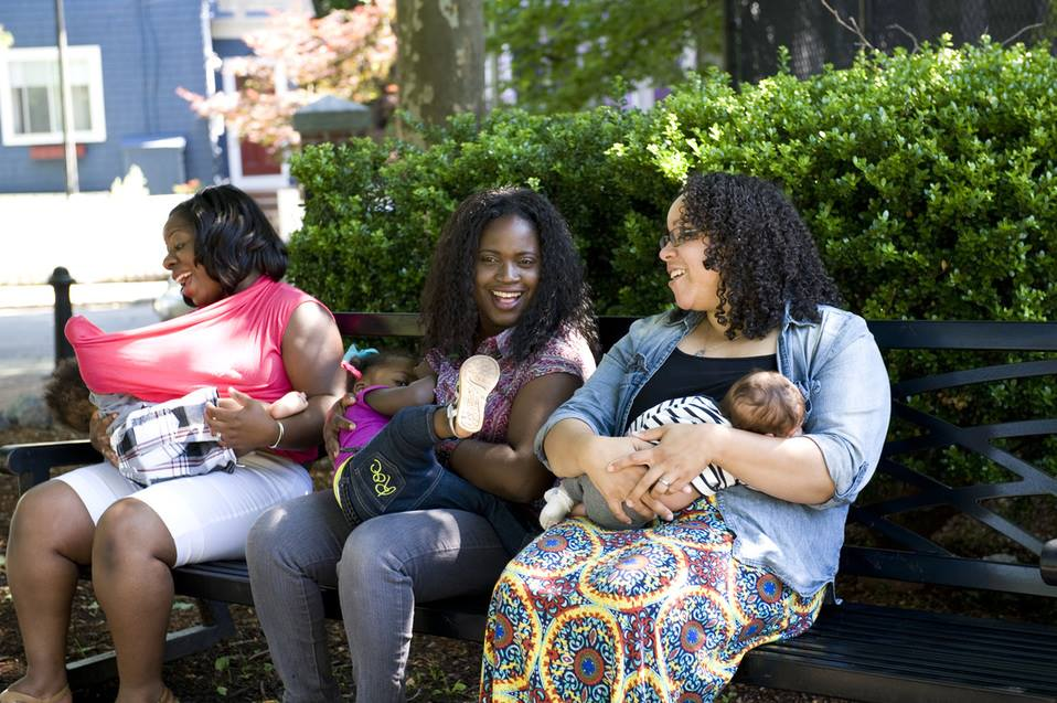 Three breastfeeding mothers on a park bench